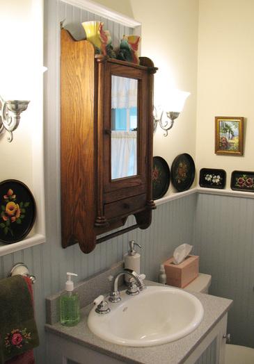 the room's garish pink wallpaper, plywood vanity, yellowed vinyl floor